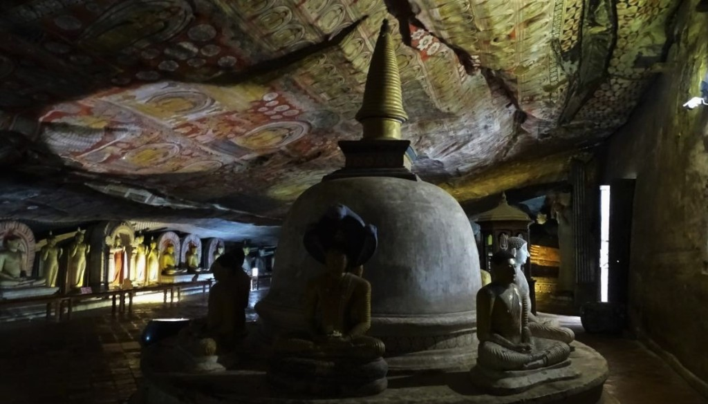 Dusky interior of Dambulla Cave Temple with natural ceiling covered with frescoes and a stupa surrounded with seated Buddha statues