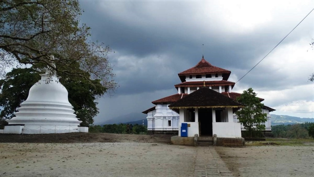 A two-storied Lankathilake temple with a white stupa next to it set against the cloudy sky