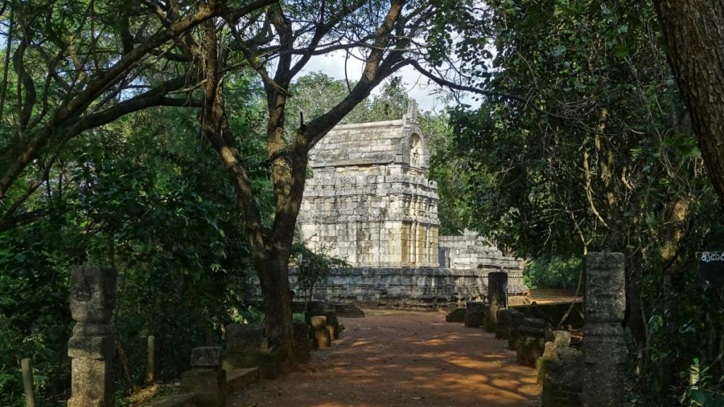 Remnants of stone collonade path through the forest lead to a small ancient stone Nalanda Gedige temple