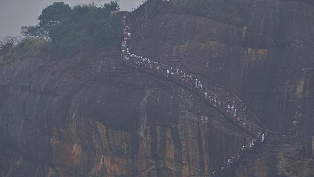 A queue of tourists snake through the entire staircase to the top of Sigiriya rock