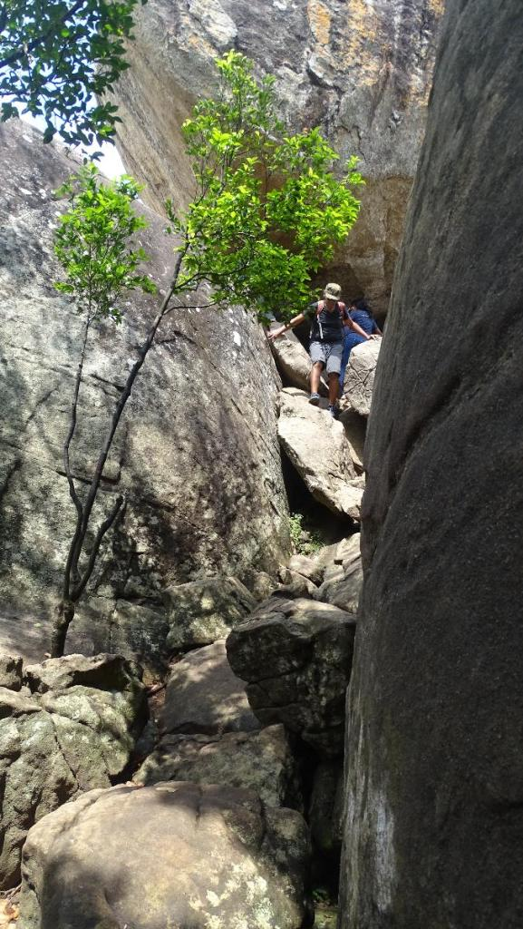 A section of vertical path among larger and smaller rocks lead to the very top of Pidurangala