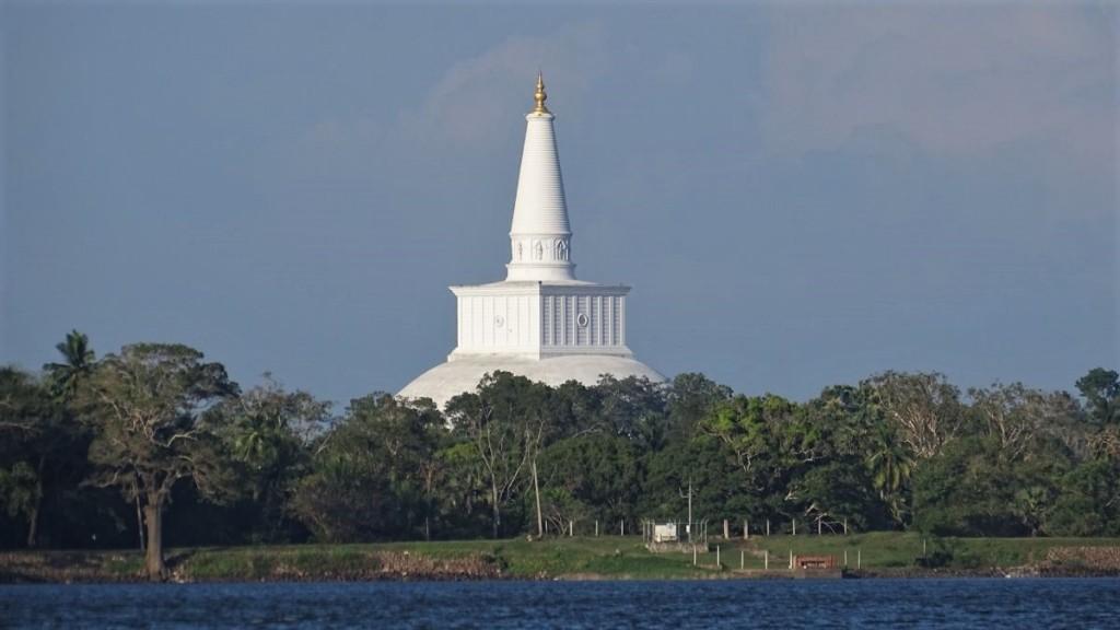 Giant, ancient stupa rises from above the treeline along the Tissa Weva lake in Anuradhapura