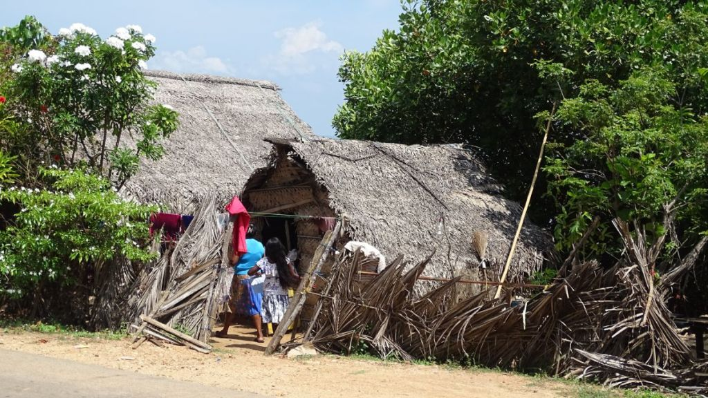 A woman with her daughter enter their hut weaved from palm leaves in Kalpitiya