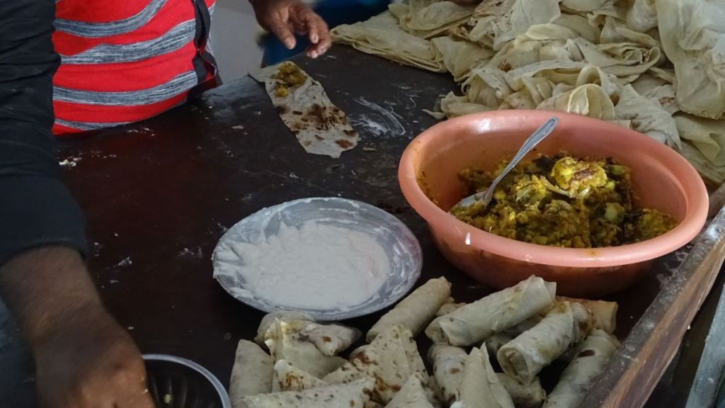 A close-up of a man placing filling into dough rolls at a budget eatery in Sri Lanka