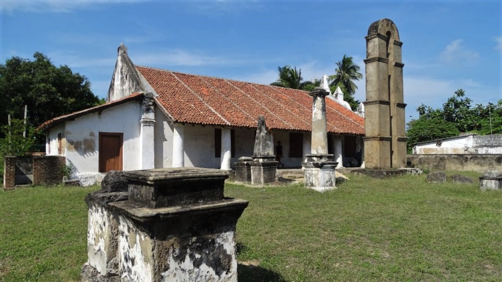 A 17th century Dutch church with white columns and a tiled roof with a few stone tombs on a graveyards