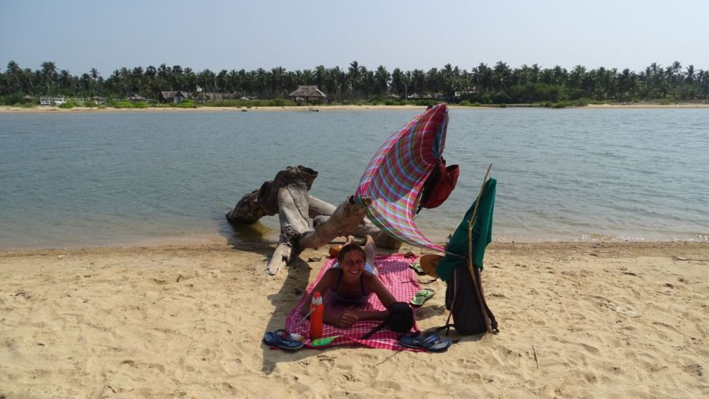 The author lies down under a make-shift shade on the beach in Kalpitiya
