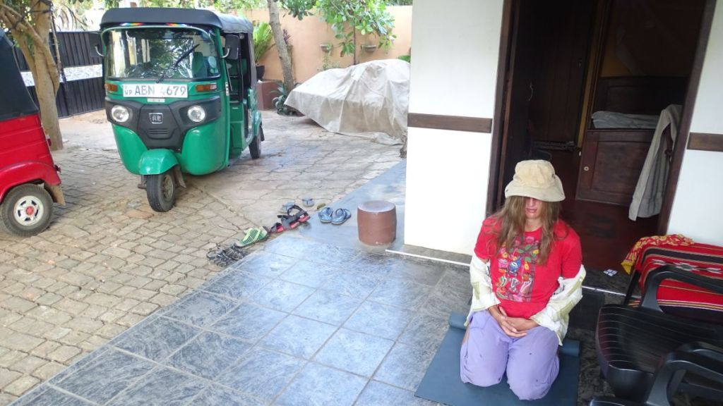 The author kneels meditating on a porch of a simple accommodation in Sri Lanka