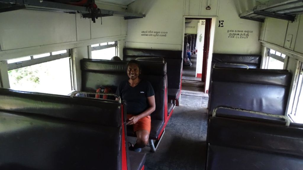Sayak sits alone in a compartnment of a third class train from Palavi to Negombo