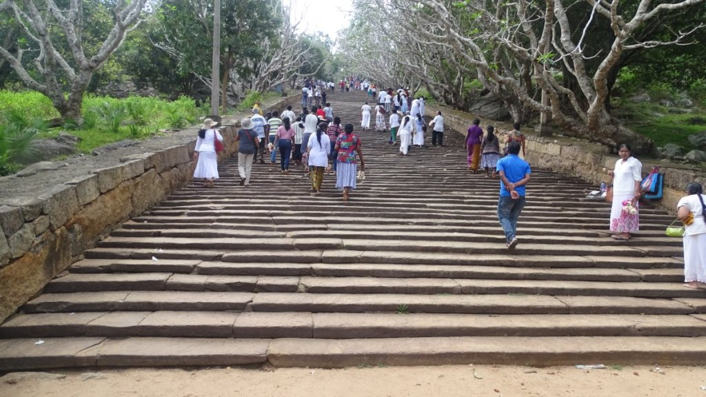 Groups of pilgrims walk up long, stone steps to Mihintale hill