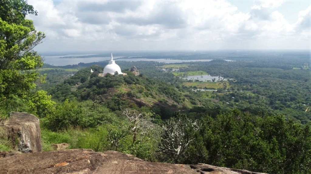 A view from Eth Vihara at Mihintale Hill with the giant white-washed stupa and the green plains and lakes below