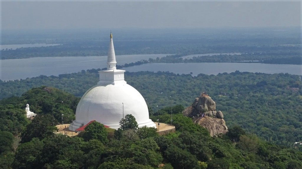 A view at Mihintale Hill with a massive, whitewashed stupa, a seated Buddha statue and a rocky outcrop filled with pilgrims, set against the backdrop of green plains and lakes below