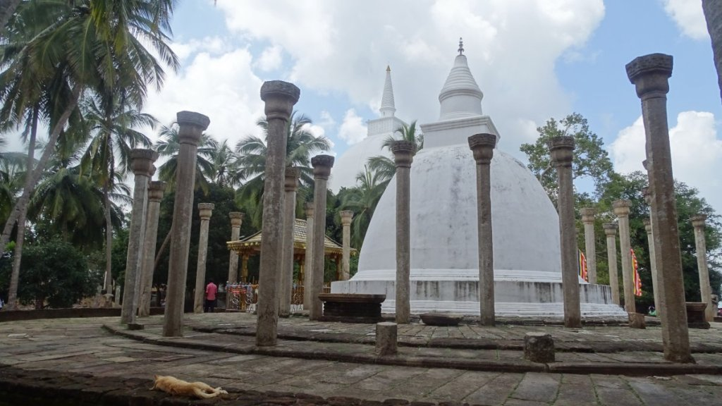 A small, white stupa is surrounded with stone pillars and a circular platform on top of Mihintale hill