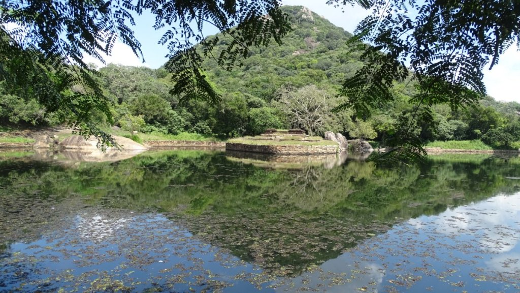 A conical, green Mihintale hill reflects in the dark waters of Kaludiya Pokuna pond