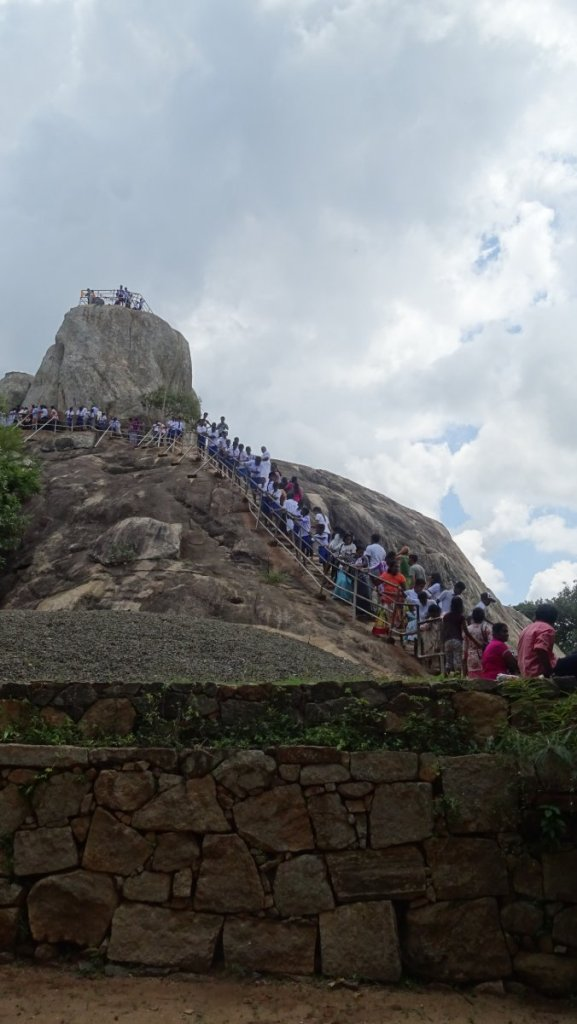 A long line of pilgrims slowly make their way up the bare rock of Aradhana Gala in Mihintale