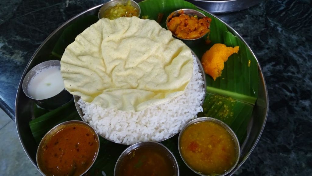 South Indian thali: a steel plate filled with rice and small bowls containing different dishes