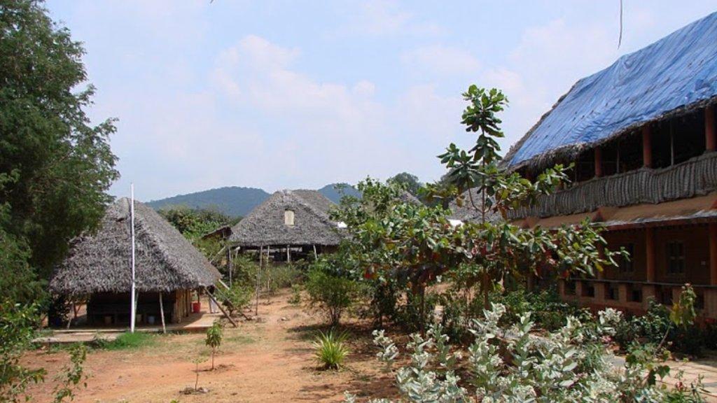 Simple, thatched-roofed edifices of the Sivananda Yoga ashram near Madurai