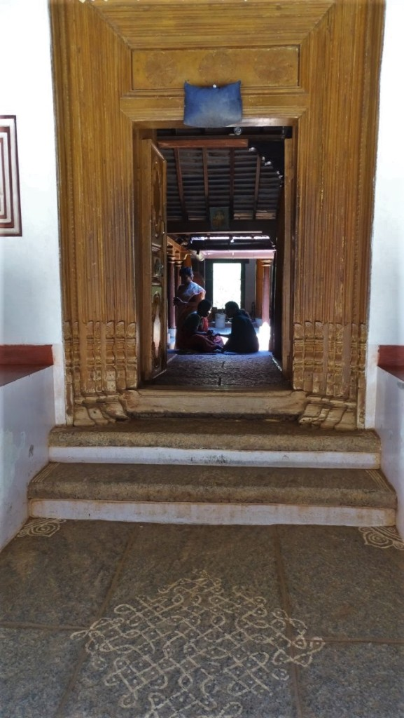 A chalk- drawn geometrical kolam pattern adorns a threshold of an old Tamil house, where women sit at a patio