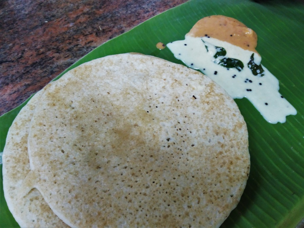 Dosas, pancakes made of fermented rice batter, served on a banana leaf with coconut chutney