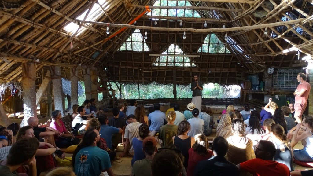 Large, roofed area at Sadhana Forest HQ, where the volunteer greets the tour of visitors sitting on the ground