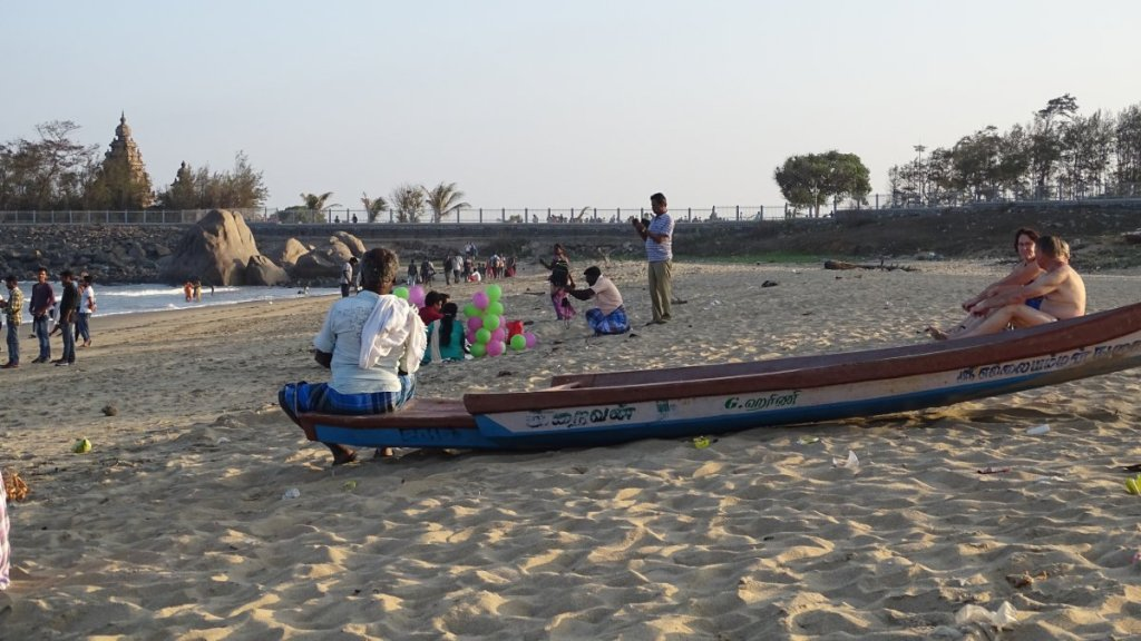 A beach in Mamallapuram with baloon- sellers, fully-dressed locals and an elderly Western couple in beach-gear.