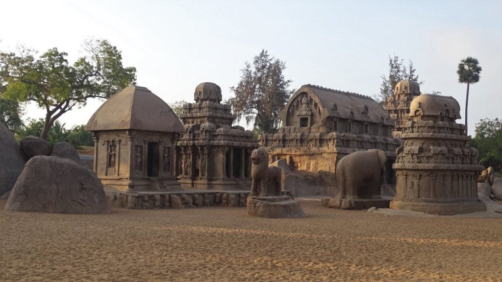 A set of small, chariot- shaped, stone temples interspersed with large statues of animals stand on the sand in Mamallapuram