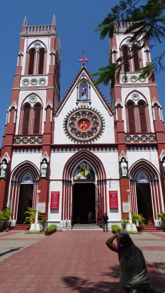 A woman in a sari covers her head before entering a tall, neo-gothic Sacred Heart Basilica in Puducherry