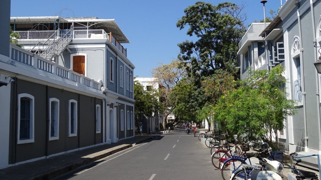 Empty, quiet street lined with renovated colonial-style buildings in Puducherry