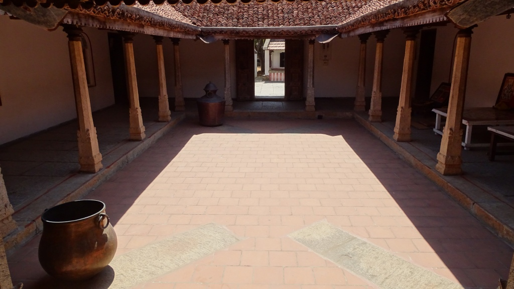 A patio of a traditional Tamil, tiled roof, one storied building with a collonaded porch at the Dakshina Chitra ethnographic part