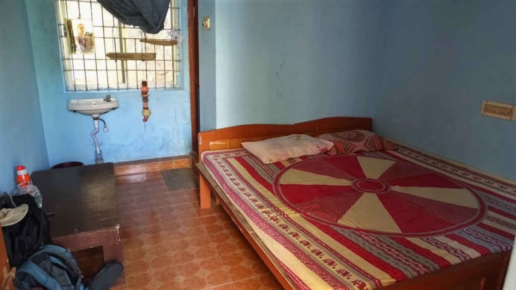 A typical budget room in India, with a bed, low table and bars in the window