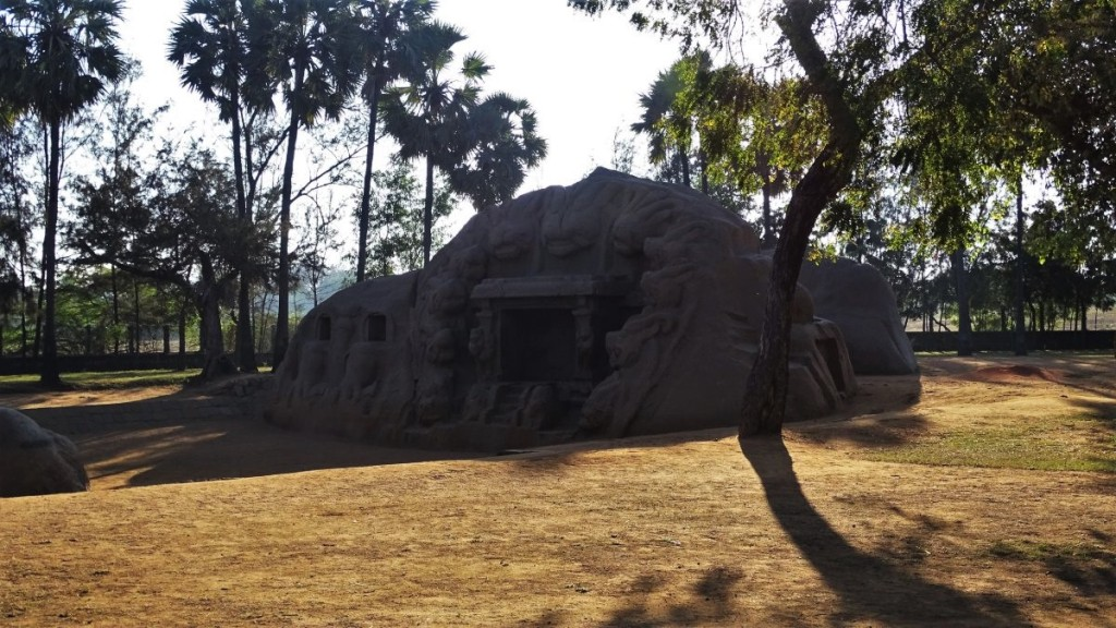 Tiger Cave- a large bulder sculpted with images of lions stands in a shade of trees near Mamallapuram