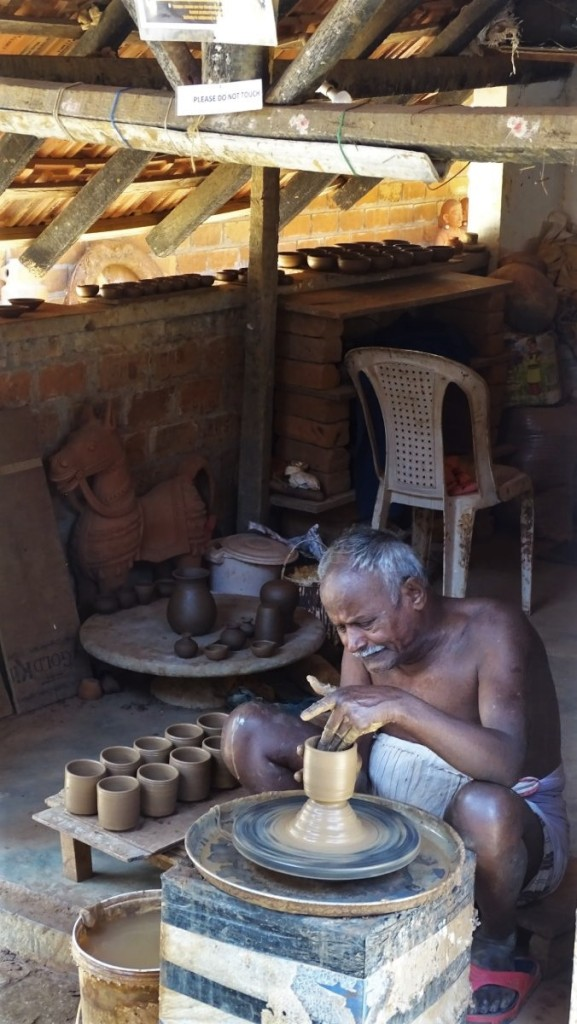 An elderly potter wearing lungi works at the potter's wheel at the Dakshina Chitra open-air museum in Tamil Nadu
