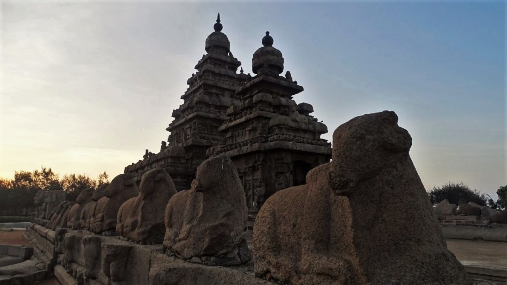 A row of stone bulls leads towards the pyramid-shaped Shore Temple in Mamallapuram