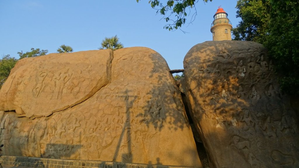 Two boulders covered with ancient reliefs and a modern lighthouse rising from behind in Mamallapuram