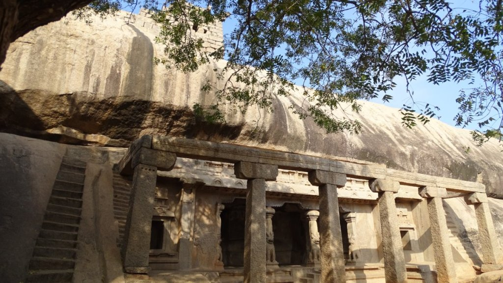 A temple cut in the rock, decorated with stone columns, some scultped, in Mamallapuram