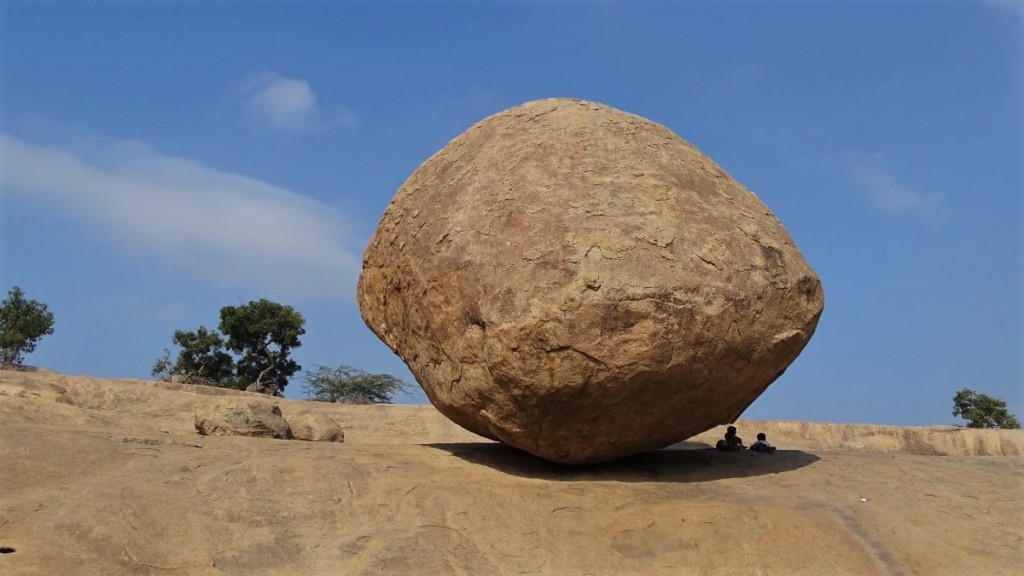Two kids sit in a shadow cast by a round rock called Krishna Butterball in Mamallapuram