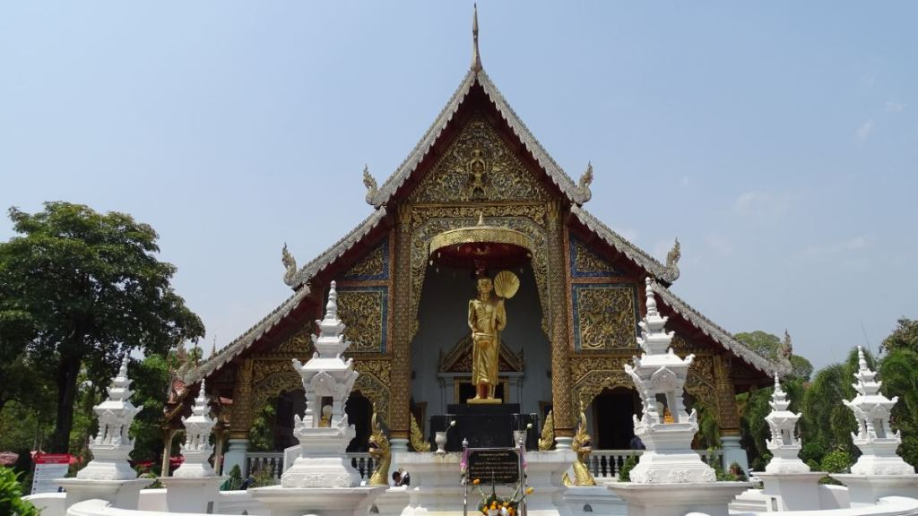 A golden gilded temple with a giant golden stateue of Buddha and small white stupas in front in Chiang Mai
